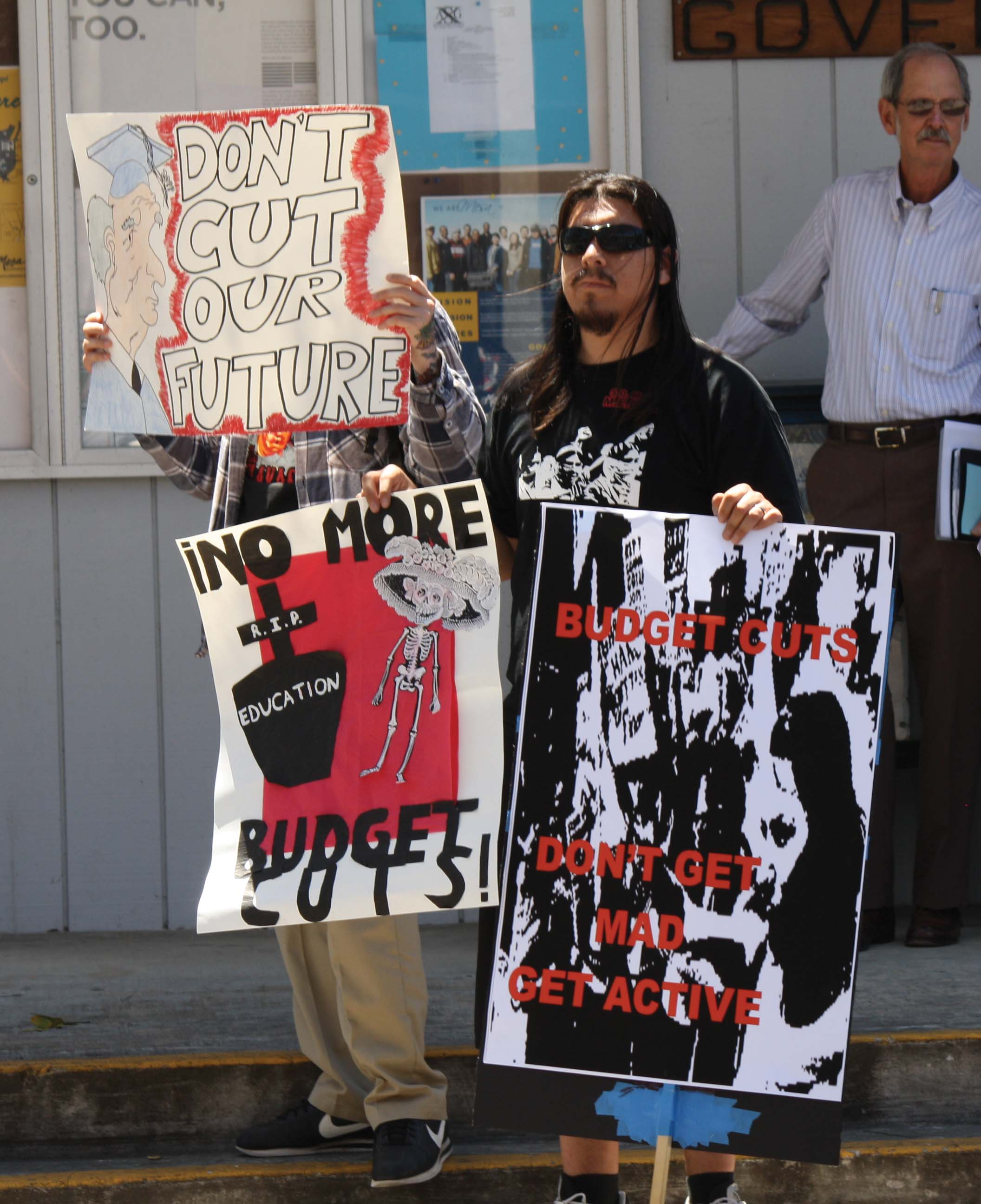 President of M.E.Ch.A, Miguel Murillo, 24, and other students brought signs to the rally to help promote action against educational budget cuts at the rally on April 27.