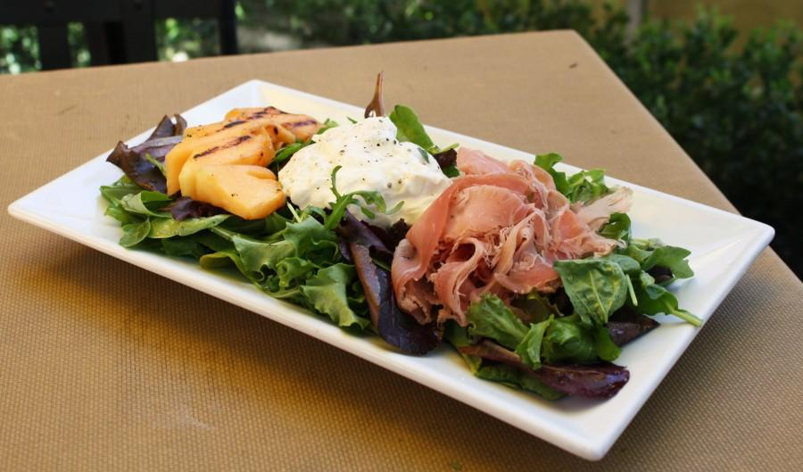 The flavoral and refreshing grilled cantaloupe salad combines the sweet melon with creamy burrata cheese and salty prosciutto atop a bed of mixed greens. [Photo Credit: Lauren J. Mapp]