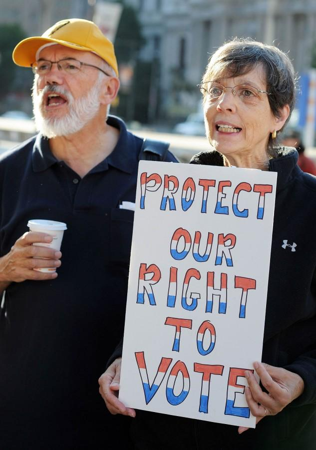 Dennis Brunn and Jill Murray of the Unitarian Society in Philadelphia, Pennsylvania cheer a speaker while holding a sign during a voter ID rally September 13, 2012 in Philadelphia, Pennsylvania. The Pennsylvania Supreme Court held a hearing on Pennsylvania's state Supreme Court justices on whether a law requiring photo identification from each voter should take effect for the Nov. 6 presidential election. (William Thomas Cain/MCT)