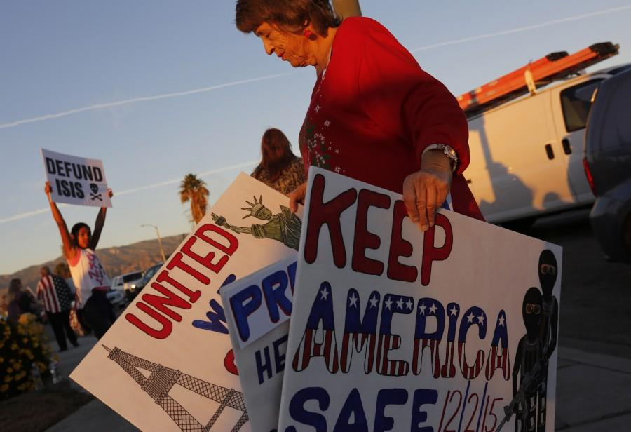 President Obama is scheduled to make a stop on Friday, Dec. 18, 2015, in San Bernardino, Calif., to privately visit the families of some of the victims of the December 2nd terrorist attack. Protesters took to street corners to voice their opposition to both Obama and ISIS, including anti-Obama protester Deann D'Lean, right, in San Bernardino on Friday evening. (Michael Robinson Chavez/Los Angeles Times/TNS)