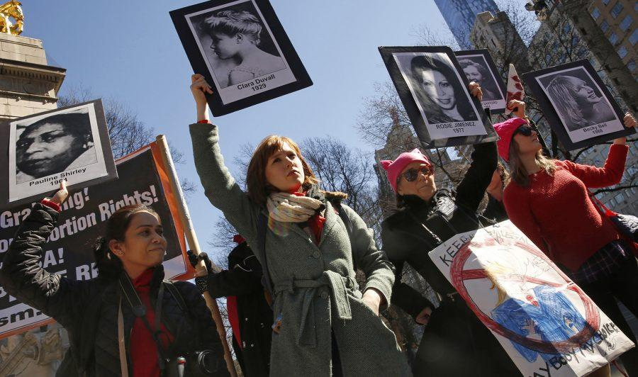 On International Womens Day, about 50 people gather on the edge of Central Park in New York to voice their opposition to the current administration policies. A group holds photographs of women who have died due to illegal abortions or no access to health care. (Carolyn Cole/Los Angeles Times/TNS)