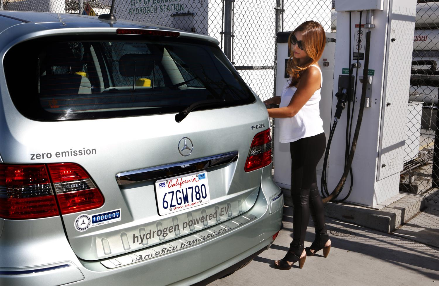 Sally Poppe, right, demonstrates filling her car at the hydrogen fuel station on Oct. 21, 2014 at Hydrogen Frontier Inc. in Burbank, Calif., owned by her husband Dan Poppe, left. Automakers are turning to another new technology - hydrogen fuel cells that have zero emissions.