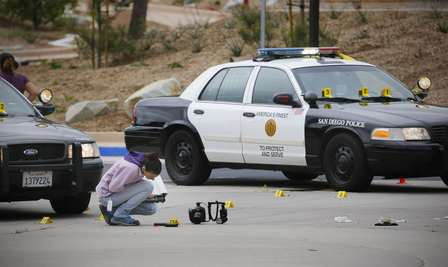 A member of the San Diego Police Department examines what appears to be a gun on the ground at the scene of a fatal police officer involved shooting of a 15-year-old boy in one of the parking lots in front of Torrey Pines High School, early Saturday morning, May 6, 2017, in San Diego, Calif. Police believe the boy called police, and when they arrived pointed a gun at them and didn't follow their commands to drop it. It turns out that the gun is a semi-automatic BB air pistol. (Howard Lipin/San Diego Union-Tribune/TNS)