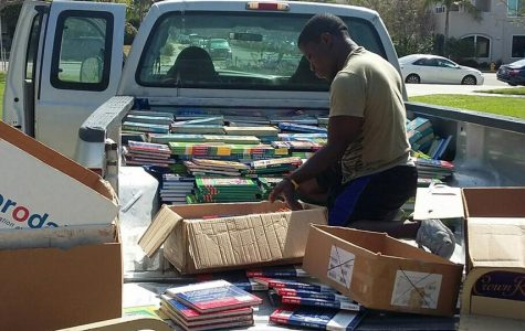 Robert Saah sorting and unloading a donation of books. (Photo Credit to the Compassion For African Villages Facebook page.)