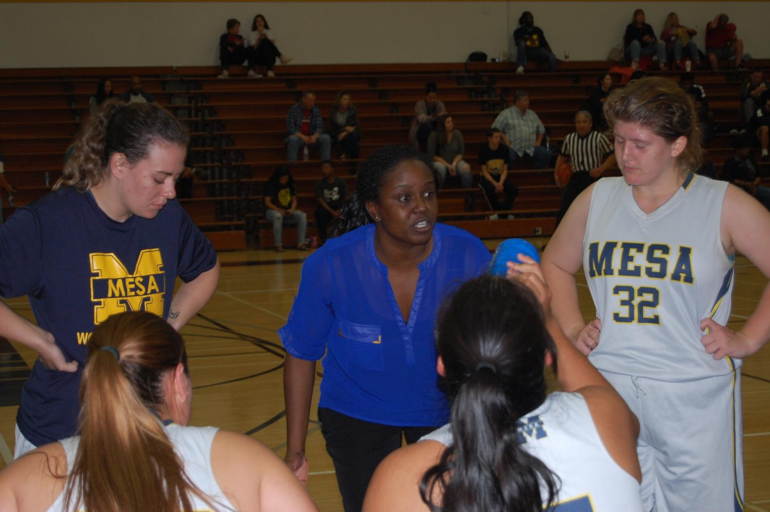 Coach Dee James talks to her team during a timeout break vs Palomar