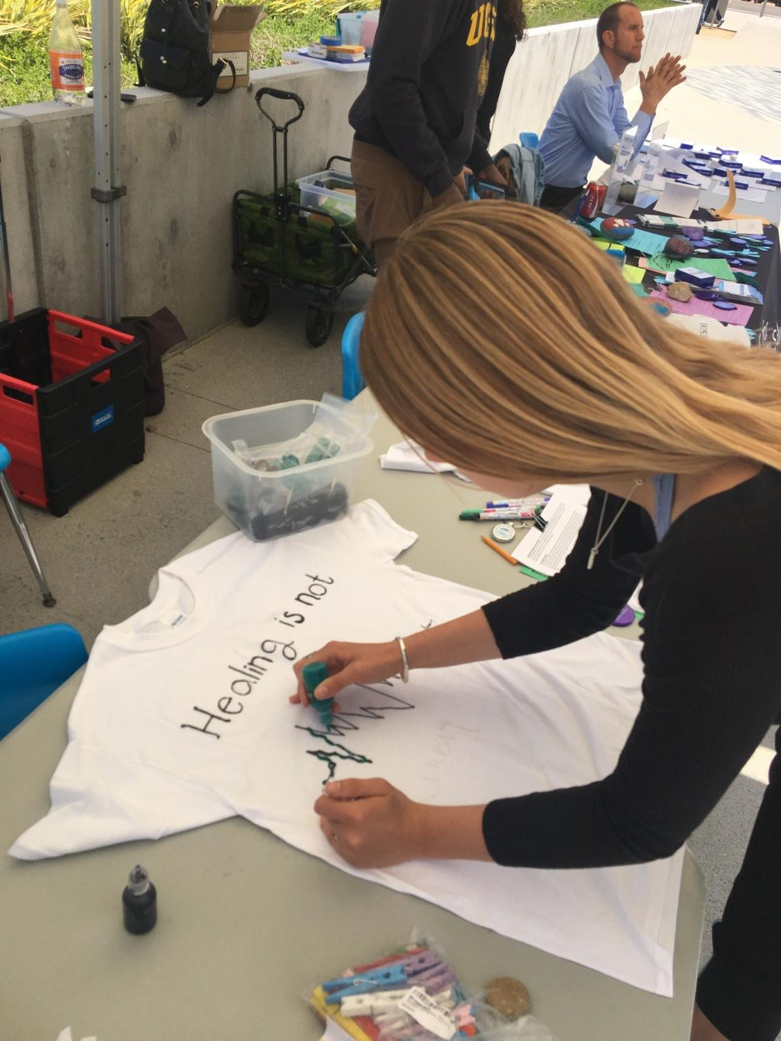 Emily Hanes, student, decorates a t-shirt with a supportive message for the Clothesline Project.