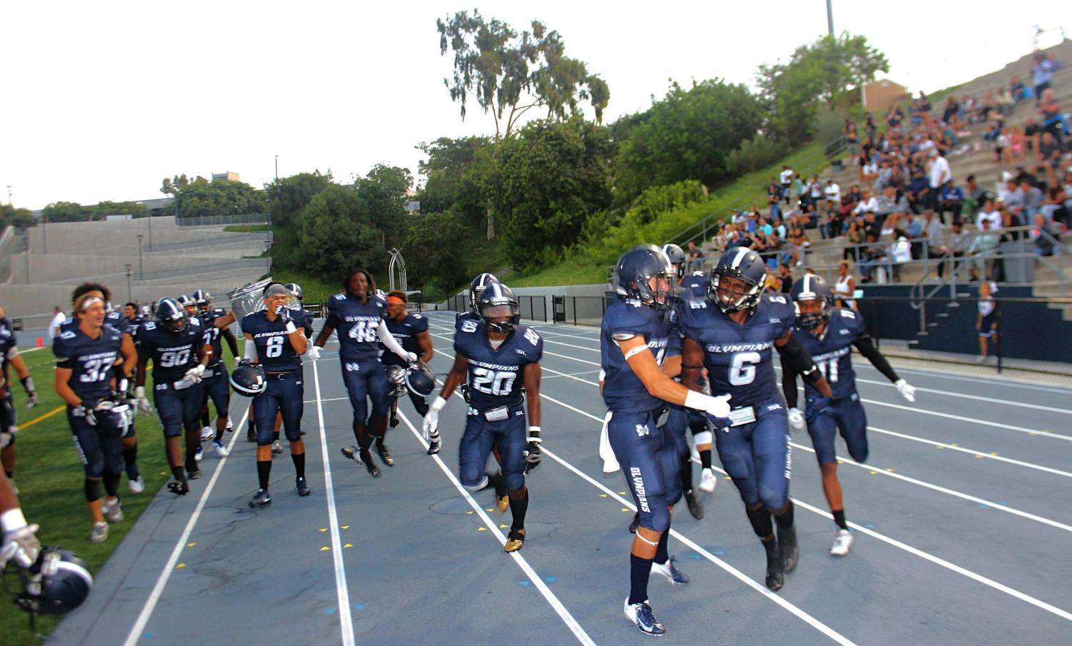 Team celebrates after LB Reginald Prince (#6) returns an interception for a touchdown in 40-14 Homecoming win.
