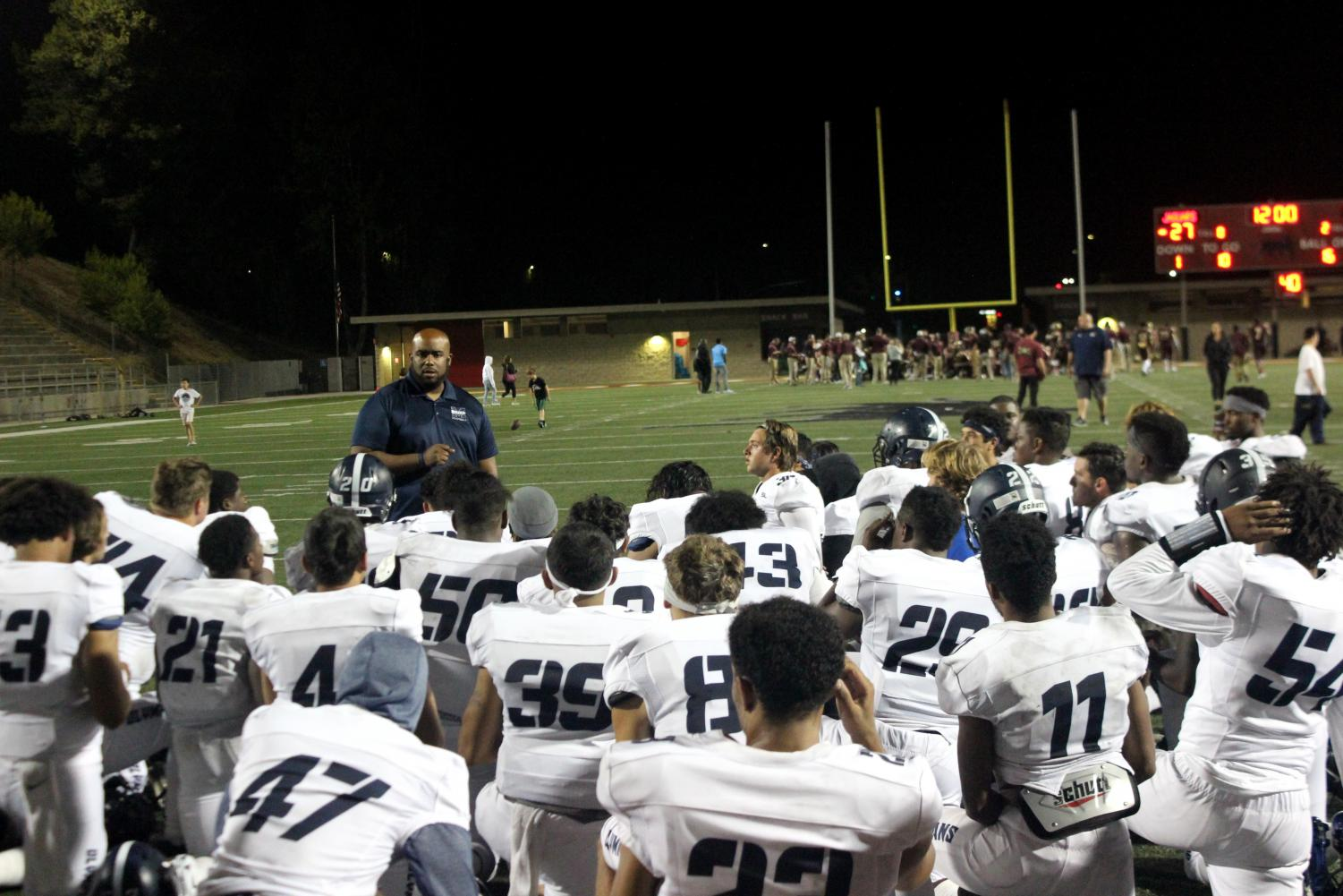 Mesa Olympians Coach Gary Watkins addresses the team on the field after their season opening loss to the Southwestern Jaguars at DeVore Stadium.