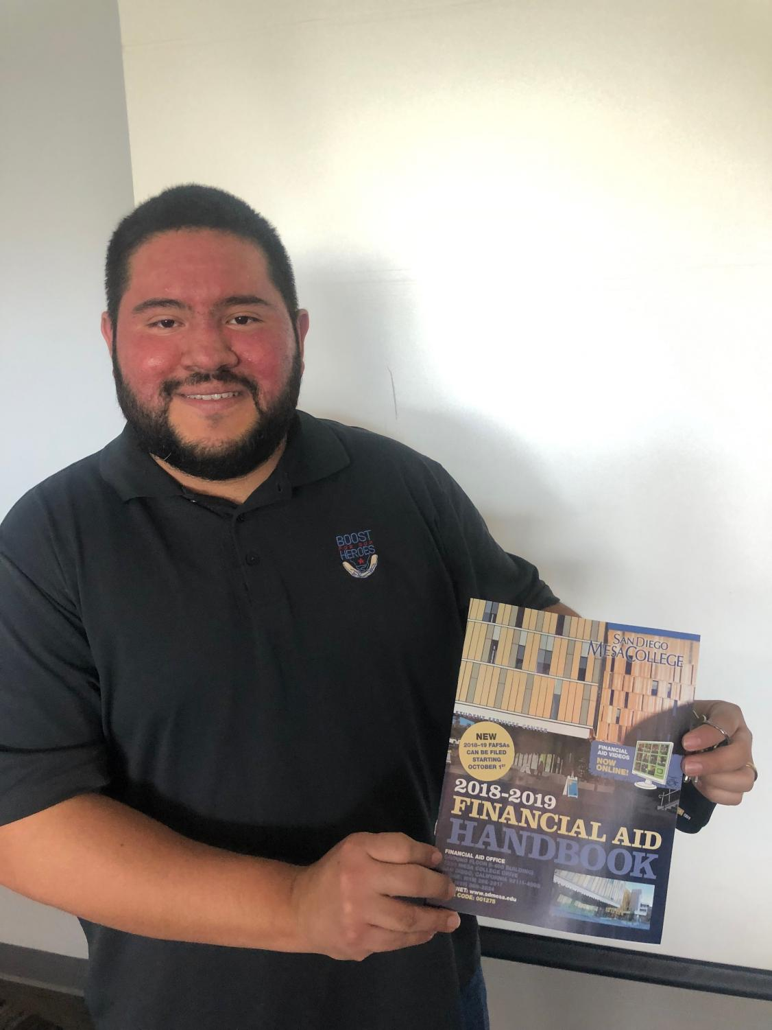 Felipe Arevalo showing off the Mesa College financial aid handbook after his presentation.