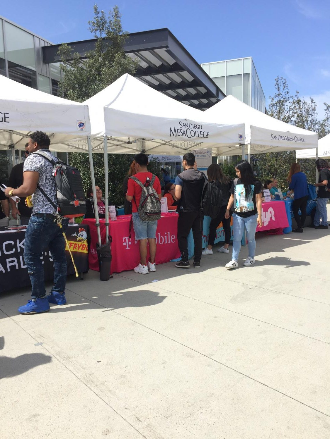 Students stop by the Chicken Charlie's, T-mobile, and Lyft booth at the job fair