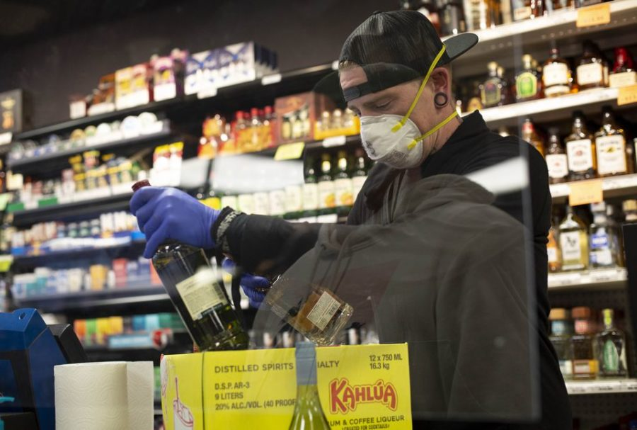 Protecting employees became a priority for business as the pandemic took hold. Here, Dustin Anderson wears a face mask and gloves, and stands behind a plastic barrier, while working at the Cedar Mill Liquor Store in Portland last March.