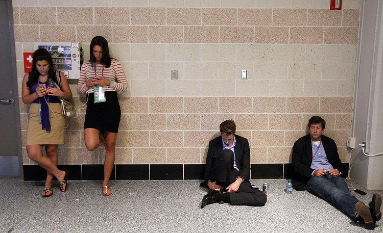 Young politicos find a quiet spot to check their smartphones at the 2012 Republican National Convention in the Tampa Bay Times Forum, Wednesday, August 29, 2012, in Tampa, Florida. (Tom Fox/Dallas Morning News/MCT)