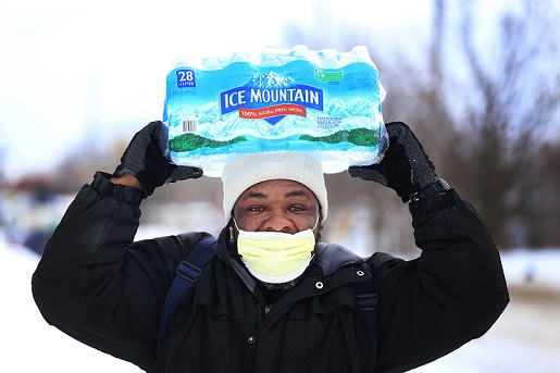 Carl Huntere, 48, of Flint, Mich., walks home through the snow from the North End Soap Kitchen in Flint on Wednesday, Jan. 13, 2016, where he received a case of free bottled water. Photo Credit: MCT Campus