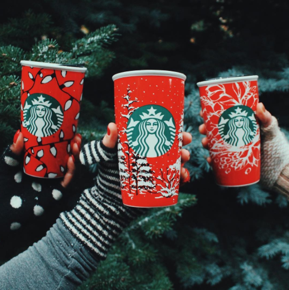 Starbucks shows off three of their 13 new cup designs.