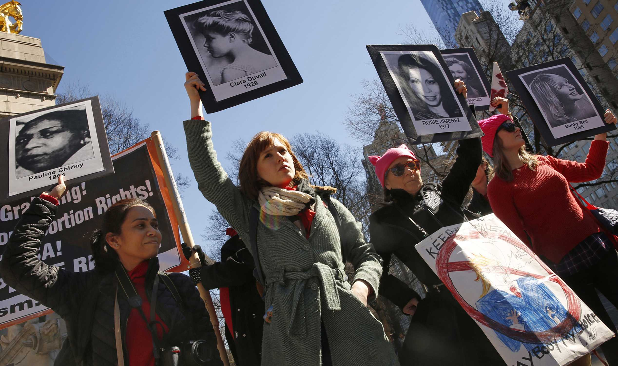 On International Women's Day, about 50 people gather on the edge of Central Park in New York to voice their opposition to the current administration policies. A group holds photographs of women who have died due to illegal abortions or no access to health care. (Carolyn Cole/Los Angeles Times/TNS)