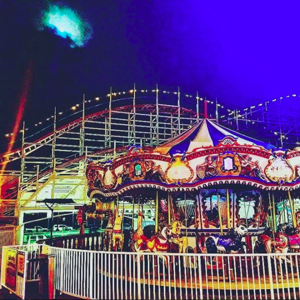 The Giant Dipper Rollercoaster at Belmont park lit up at night.