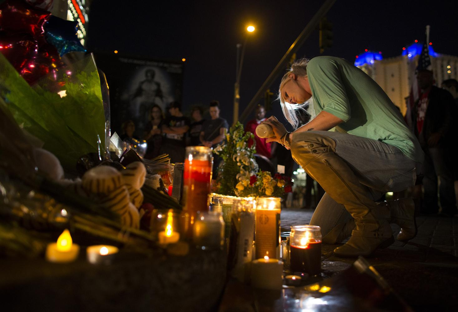 Kaili Berdge of Scottsdale, Ariz. makes sure every candle stays lit Wednesday, Oct. 4, 2017 at a memorial for the victims of the mass shooting near the crime scene off Las Vegas Boulevard in Las Vegas, Nev. (Gina Ferazzi/Los Angeles Times/TNS)