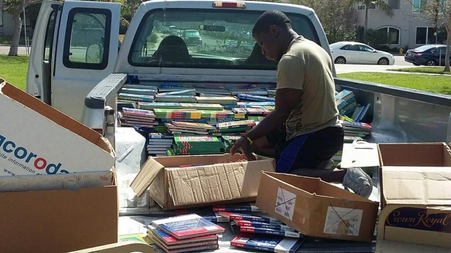 Robert+Saah+sorting+and+unloading+a+donation+of+books.+%28Photo+Credit+to+the+Compassion+For+African+Villages+Facebook+page.%29+
