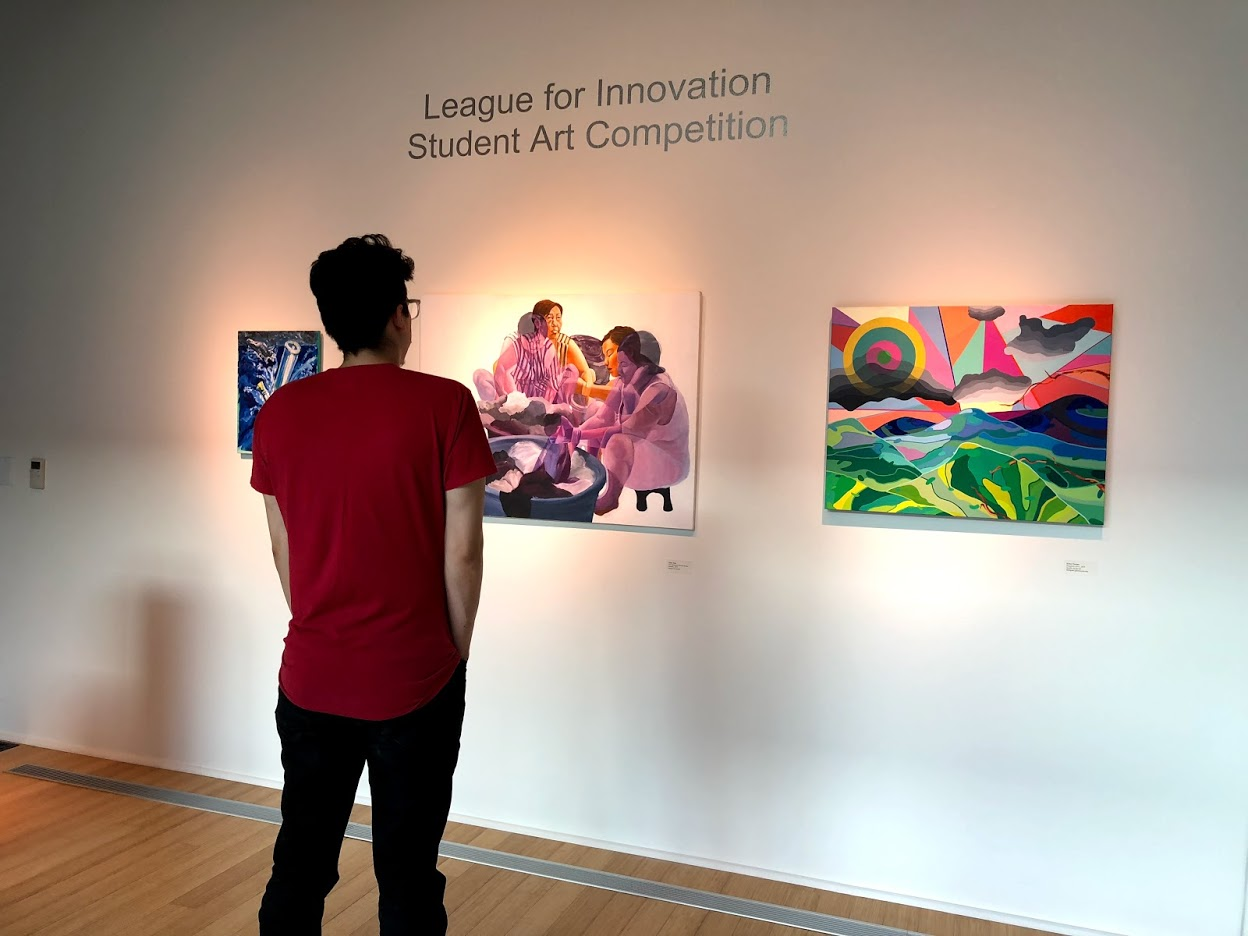 A man who attended the show admiring a piece by artist Jenny Tran.