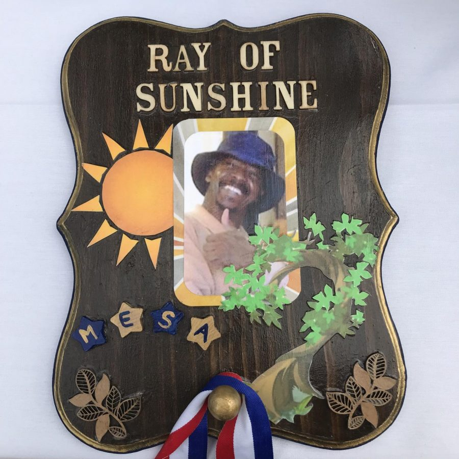 Co-workers make a small plaque to remember and honor close friend Ray Vital.