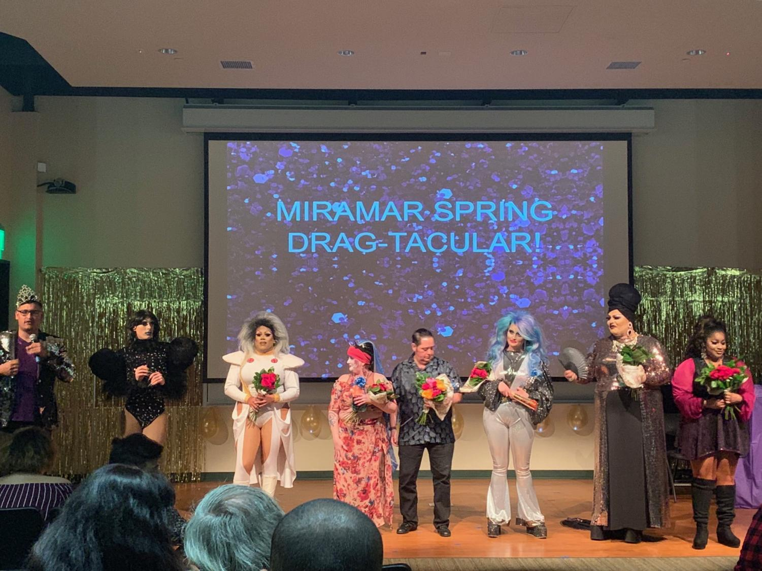 (From left to right)  Host Carlos Trujillo stands with performers Sienna Desire, Vanity Jones, Sister Develyn Angels, Rudy, Mercury Dee, Barbie Z, and Delicious Jones, as they accept flowers as a gift from Miramar's LGBTQ+ Alliance.