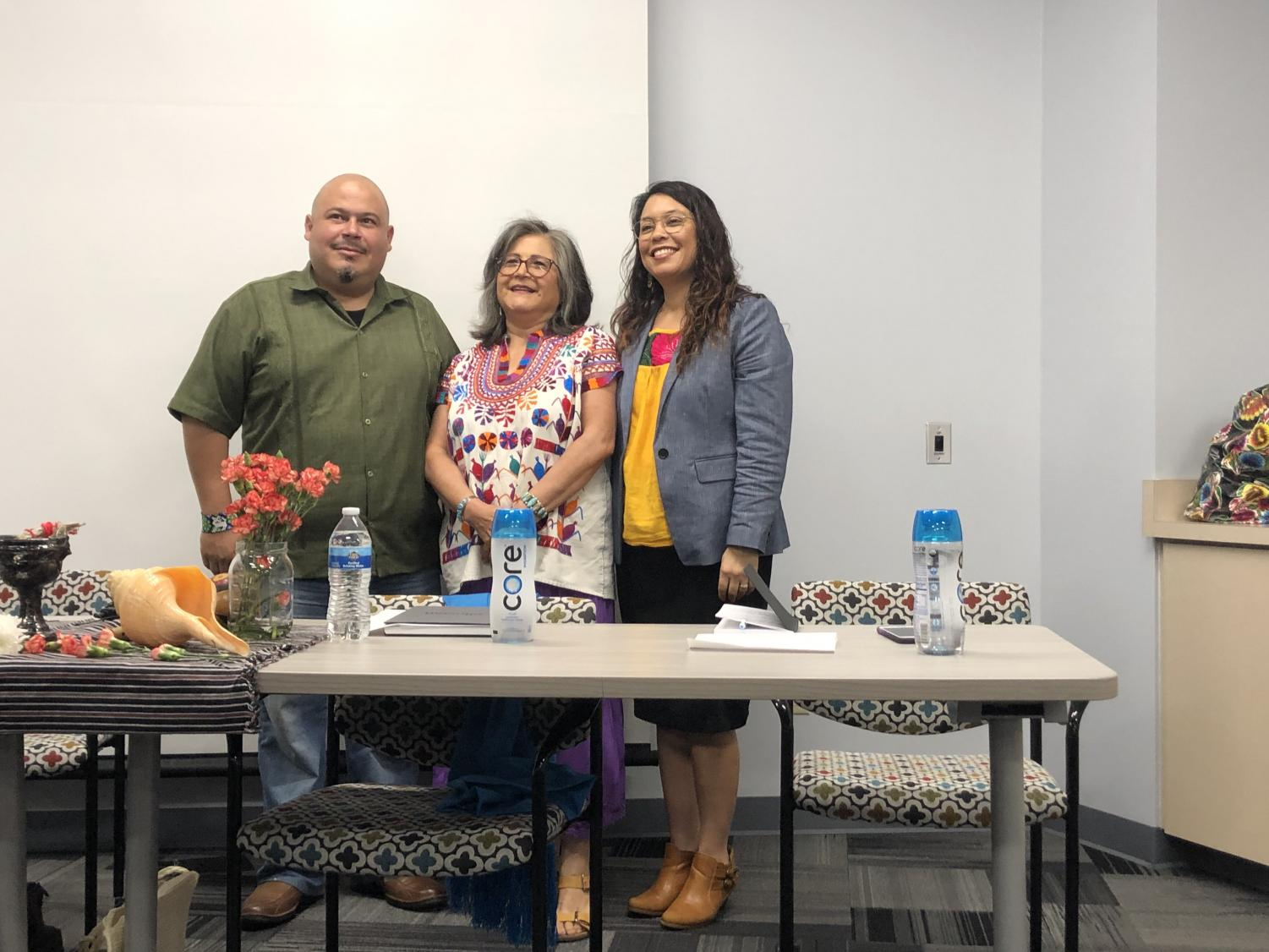 From left to right,  panelists Roberto D. Hernandez, Maria Figueroa and Bea Zamora pose as Mesa students take their picture  to commemorate the Danza Azteca event.