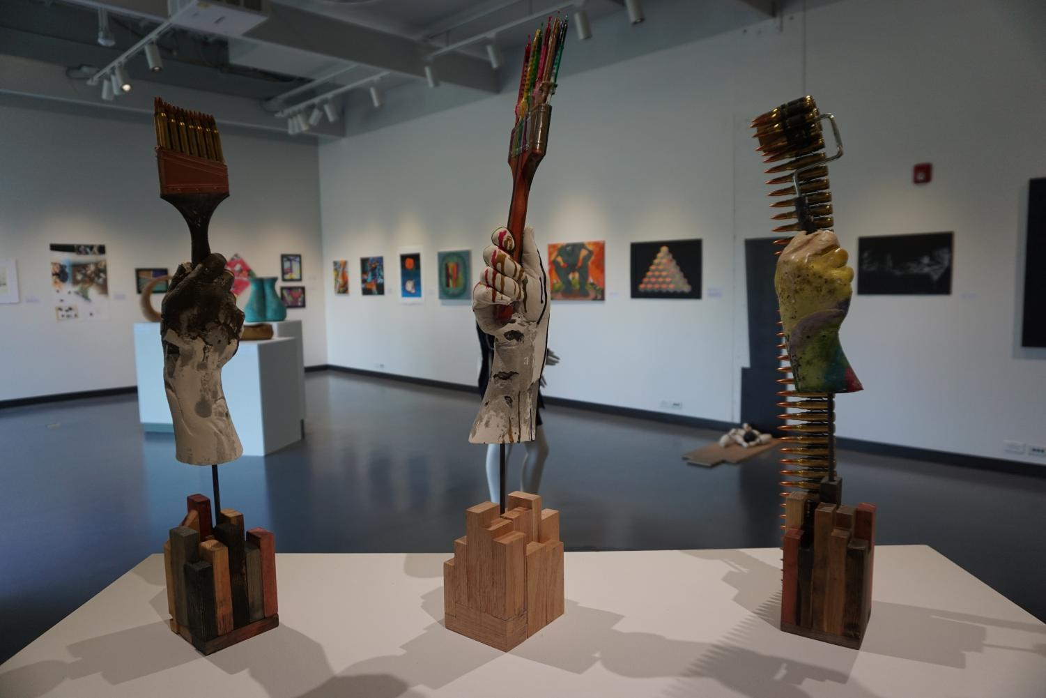 Lourans Michail's mixed media sculpture features a trio of fists holding weaponized art instruments. Artwork is titled