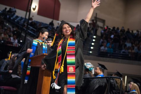 A Mesa student proudly waves during the spring 2019 Commencement Ceremony, now a thing of the past. Photo Credit: Mesa Office of Communications